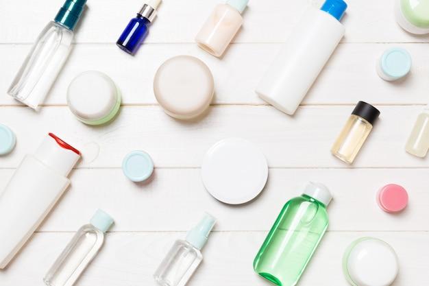Vista superior de diferentes frascos de cosméticos e recipiente para cosméticos em branco de madeira