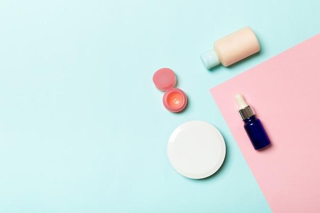 Vista superior de diferentes frascos de cosméticos e recipiente para cosméticos em fundo rosa e azul. composição plana leiga com espaço de cópia