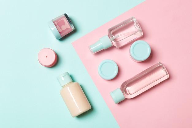 Vista superior de diferentes frascos de cosméticos e recipiente para cosméticos em rosa e azul. composição plana leiga com copyspace