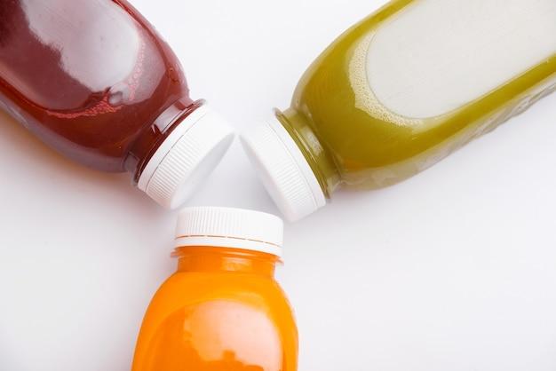 Vista superior de diferentes frascos de suco desintoxicante, antioxidantes e vitaminas diárias de que você precisa