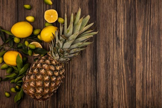 Vista superior de diferentes frutas frescas, como abacaxi, limão e kinkans, isolados em uma parede de madeira com espaço de cópia