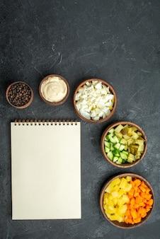 Vista superior de diferentes ingredientes de salada vegetais fatiados em superfície escura