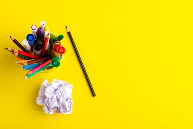 Vista superior de diferentes lápis com canetas hidrográficas na superfície amarela