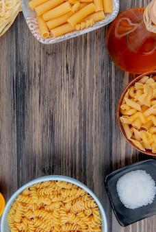 Vista superior de diferentes macaronis como tagliatelle ziti rotini e outros com sal de manteiga derretida na madeira com espaço de cópia