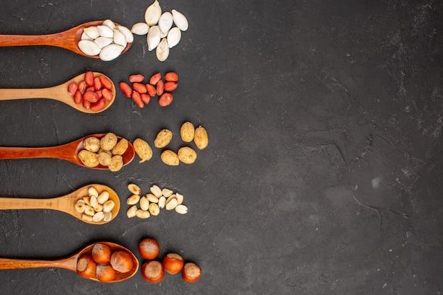 Vista superior de diferentes nozes frescas, amendoim e outras nozes na superfície escura