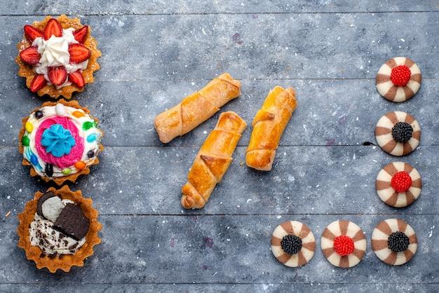 Vista superior de diferentes pequenos bolos com frutas fatiadas, bombons, pulseiras de chocolate e bagas em cinza, biscoito biscoito doce açúcar assado