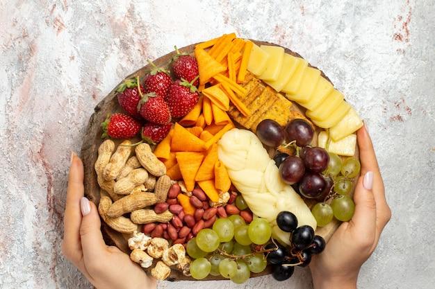 Vista superior de diferentes petiscos deliciosos uvas frescas cips queijo e nozes na superfície branca