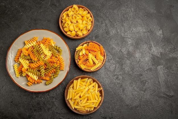 Vista superior de diferentes produtos crus de composição de massa dentro de pratos em cinza
