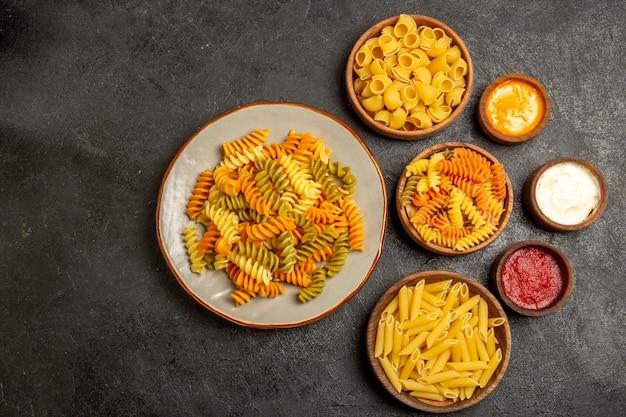 Vista superior de diferentes produtos crus de composição de massa dentro de pratos na mesa cinza
