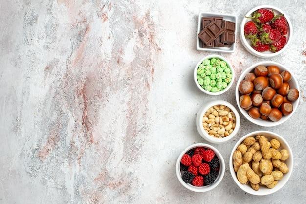 Vista superior de diferentes salgadinhos, amendoins, avelãs e doces na superfície branca