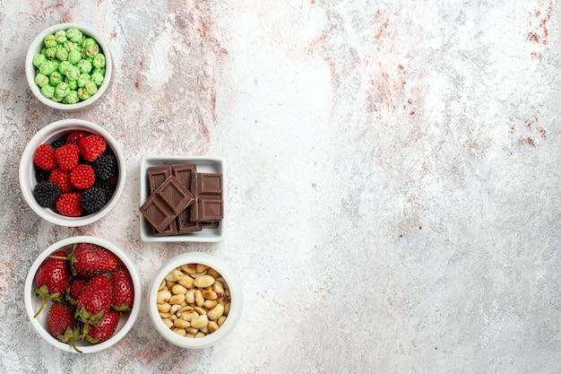 Vista superior de diferentes salgadinhos, amendoins, frutas e doces em uma superfície branca clara