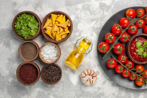 Vista superior de diferentes temperos com tomate cereja na mesa branca