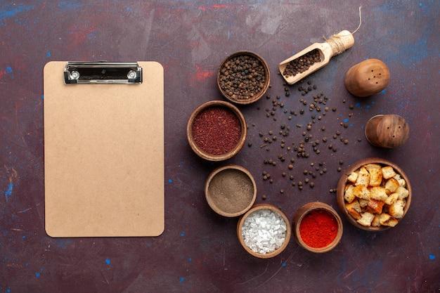 Vista superior de diferentes temperos com tostas secas e bloco de notas na mesa escura