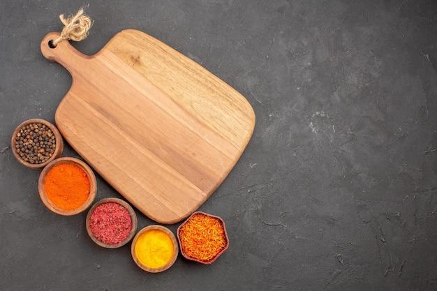 Vista superior de diferentes temperos e ingredientes picantes dentro de pequenas panelas em preto