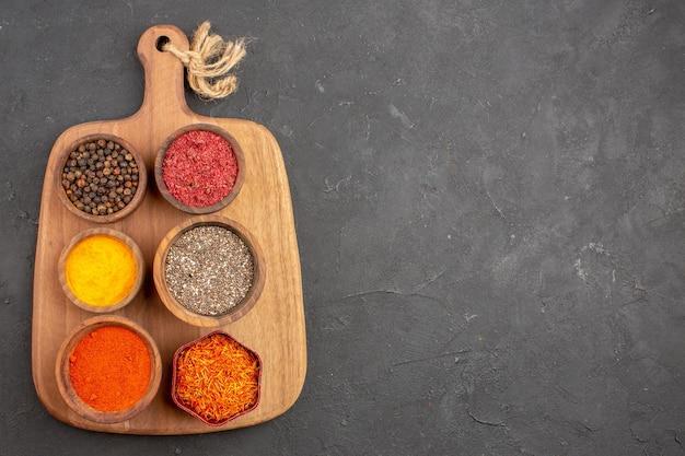 Vista superior de diferentes temperos, ingredientes picantes dentro de potes em preto