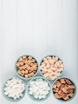 Vista superior de diferentes tipos de açúcar em cubas em fundo branco, com espaço de cópia