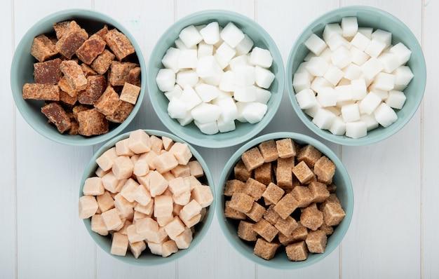 Vista superior de diferentes tipos de açúcar protuberante em tigelas em fundo branco