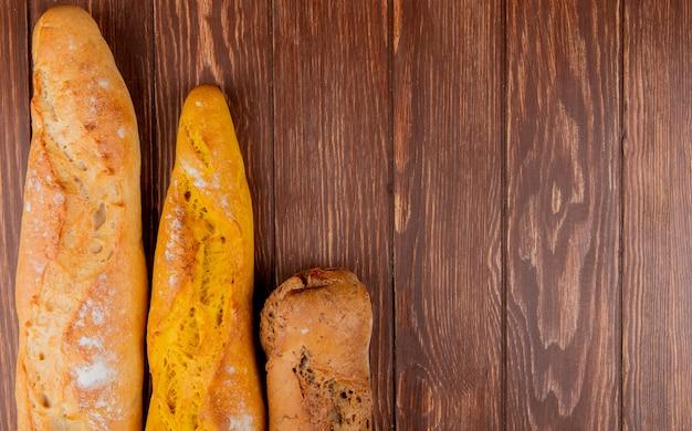 Vista superior de diferentes tipos de baguete em fundo de madeira com espaço de cópia