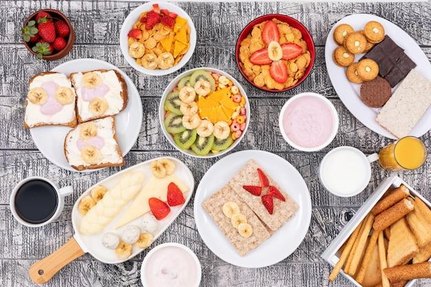 Vista superior de diferentes tipos de café da manhã como torradas, flocos de milho, iogurte e frutas