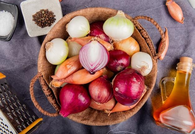 Vista superior de diferentes tipos de cebola na cesta com sal pimenta preta sementes derretidas ralador de manteiga em torno de pano cinza