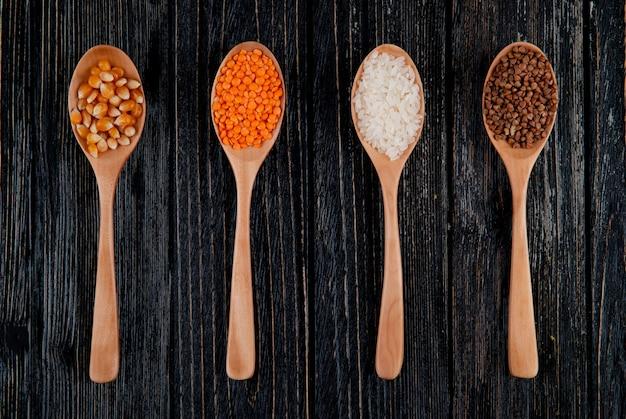 Vista superior de diferentes tipos de cereais e sementes em colheres de madeira, sementes de milho, arroz de lentilha vermelha e trigo sarraceno
