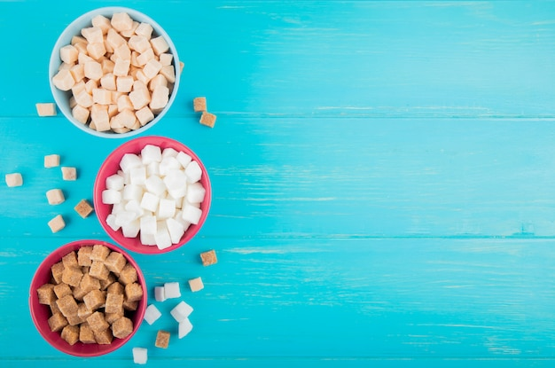 Vista superior de diferentes tipos de cubos de açúcar em tigelas sobre fundo azul de madeira, com espaço de cópia
