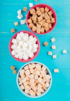 Vista superior de diferentes tipos de cubos de açúcar em tigelas sobre fundo azul de madeira