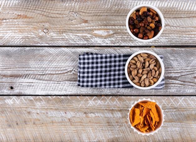 Vista superior de diferentes tipos de lanches como chips de nozes no guardanapo com espaço de cópia no fundo de madeira branco horizontal
