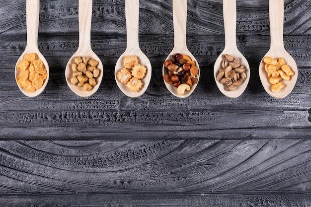 Vista superior de diferentes tipos de lanches como nozes e biscoitos em colheres de madeira, com espaço de cópia no fundo escuro horizontal