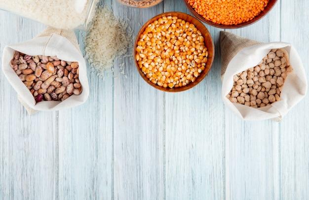 Vista superior de diferentes tipos de legumes e cereais feijão arroz arroz calos lentilhas vermelhas e grão de bico em sacos e tigelas em fundo rústico com espaço de cópia