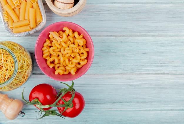 Vista superior de diferentes tipos de macarrão como espaguete cavatappi ziti com sal de tomate na madeira com espaço de cópia