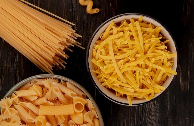Vista superior de diferentes tipos de macarrão como tagliatelle e outros em tigelas com espaguete na superfície de madeira