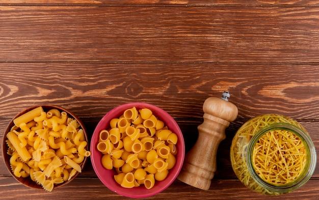 Vista superior de diferentes tipos de macarrão em tigelas e sal na madeira com espaço de cópia