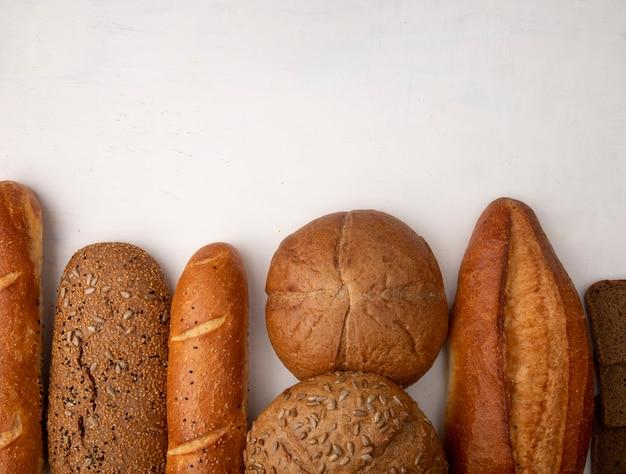 Vista superior de diferentes tipos de pão como baguette cob centeio em fundo branco, com espaço de cópia