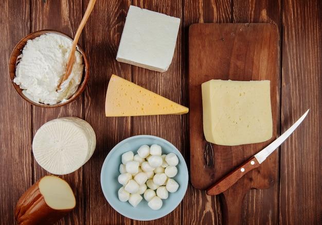 Vista superior de diferentes tipos de queijo na mesa de madeira rústica