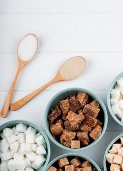 Vista superior de diferentes tipos e formas de açúcar em tigelas e colheres de pau no fundo branco