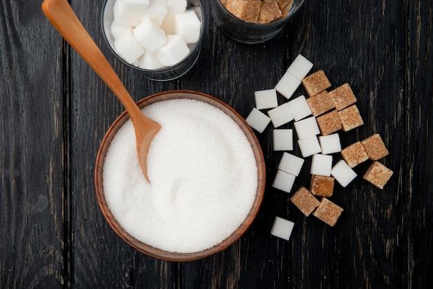 Vista superior de diferentes tipos e formas de açúcar em uma tigela e copos em fundo preto de madeira