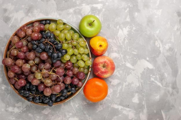 Vista superior de diferentes uvas com outras frutas na mesa branca clara