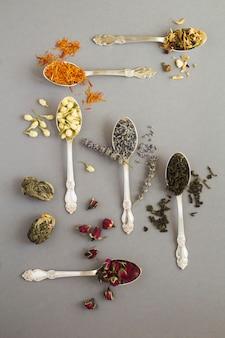 Vista superior de diferentes variedades de chá nas colheres de prata no fundo cinza