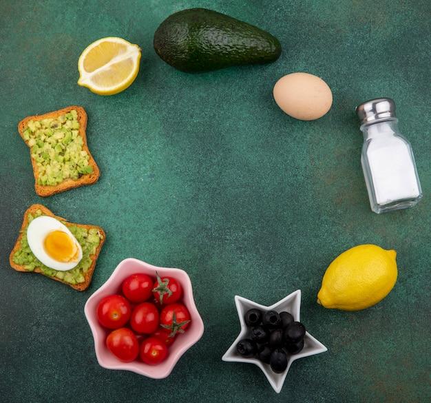 Vista superior de diferentes vegetais, como tomates, azeitonas, limão, polpas de abacate em pão torrado com ovo cozido em verde com espaço de cópia