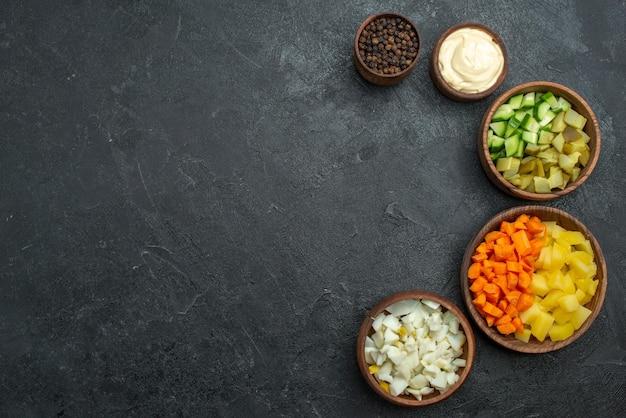 Vista superior de diferentes vegetais fatiados na superfície escura refeição lanche salada de vegetais