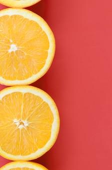 Vista superior de diversas fatias alaranjadas da fruta no fundo brilhante na cor vermelha. uma imagem saturada de textura cítrica