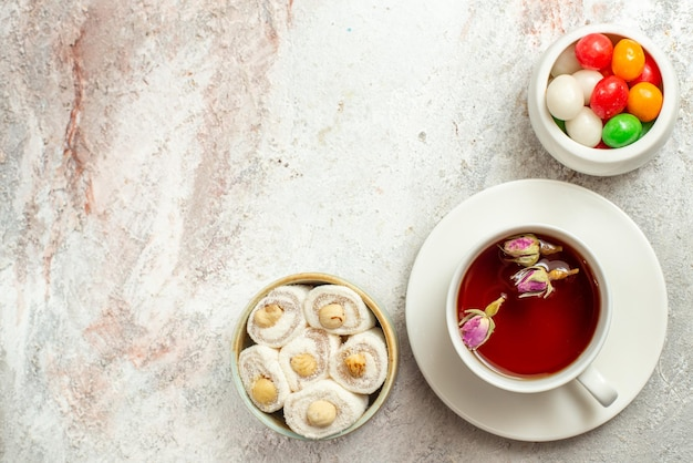 Vista superior de doces à distância com uma xícara de chá tigelas de doces deliciosos turcos e uma xícara de chá no fundo branco