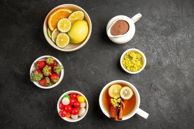Vista superior de doces à distância nas tigelas de mesa de ervas e morangos ao lado da xícara de chá de ervas com limão e canela em pau
