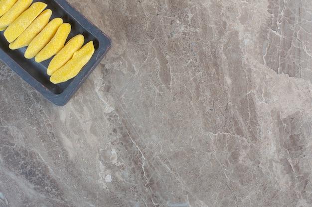 Vista superior de doces amarelos em uma fileira na placa de madeira.