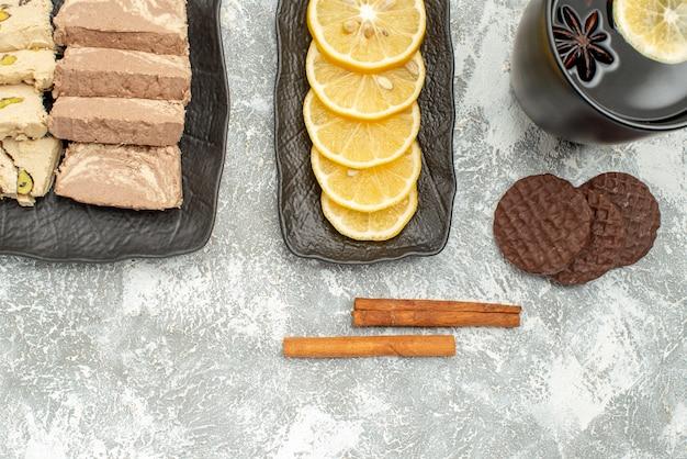 Vista superior de doces, canela, uma xícara de chá, limão, semente de girassol, halva, no prato
