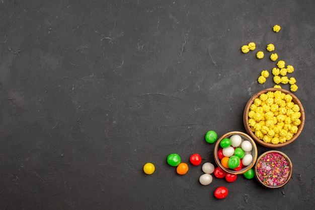 Vista superior de doces coloridos no espaço escuro