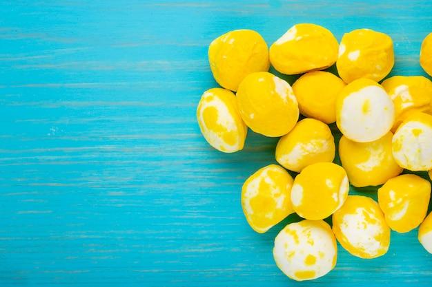 Vista superior de doces de açúcar doce amarelo sobre fundo azul de madeira, com espaço de cópia