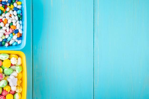 Vista superior de doces de açúcar doce colorido em taças sobre fundo azul de madeira, com espaço de cópia