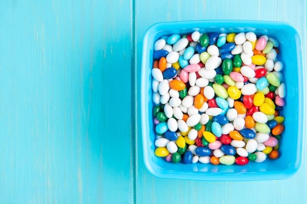 Vista superior de doces de açúcar doce colorido em uma tigela sobre fundo azul de madeira, com espaço de cópia
